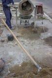 Cimento de mistura do trabalhador do construtor, pá no primeiro plano Foto de Stock