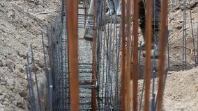 Cimento e concreto de derramamento do trabalhador com tubo de bomba filme