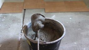 Cimento esparadrapo misturado completo da cubeta no assoalho Trabalho do construtor filme