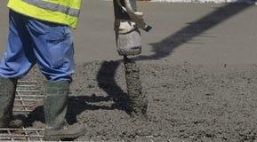 Cimento ou concreto de derramamento do trabalhador de construção civil com tubo de bomba fotos de stock