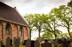 Cimetière avec l'église et les pierres tombales Images libres de droits