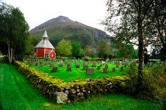 Cimetière avec une église rouge dans les montagnes Photographie stock libre de droits