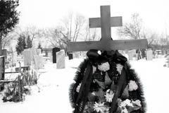 Cimitero durante l'inverno nella priorità alta un incrocio sulla tomba con una corona dei fiori artificiali, nella pietra tombale Fotografia Stock Libera da Diritti