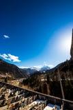 Cimitero sotto un picco nevoso dell'alpe in un giorno di molla Fotografie Stock Libere da Diritti