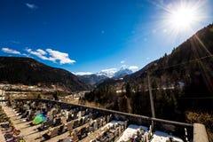 Cimitero sotto un picco nevoso dell'alpe in un giorno di molla soleggiato Immagine Stock