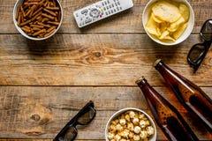 Cinéma et TV whatching avec de la bière, des miettes, des puces et la maquette en bois de vue supérieure de fond de maïs de bruit Photos stock