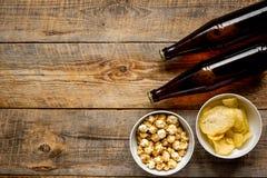 Cinéma et TV whatching avec de la bière, les pommes chips et la maquette en bois de vue supérieure de fond de maïs de bruit Photos stock
