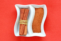 Cinamon sticks and cinamon powder on a plate. Stock Images