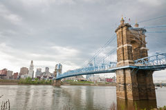 Cincinnati, OH and the Ohio River. Image of Cincinnati skyline and historic suspension bridge cross Ohio River on an overcast day. The historic John A. Roebling Stock Photos