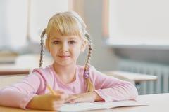 Cinco años de la muchacha rubia que se sienta en la sala de clase y la escritura Fotografía de archivo libre de regalías