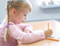 Cinco años de la muchacha rubia que se sienta en la sala de clase y la escritura Imagen de archivo