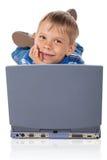 Cinco años del muchacho con la computadora portátil Fotos de archivo
