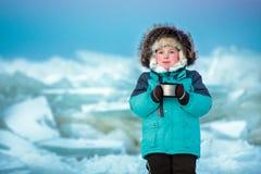Cinco años lindos del muchacho que bebe té caliente en el mar congelado invierno Imagen de archivo libre de regalías