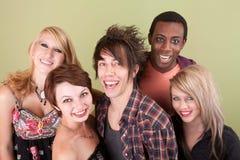 Cinco adolescencias urbanas de risa delante de la pared verde Imagen de archivo
