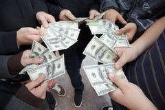 Cinco adolescentes que permanecem com divertimentos dos dólares nas mãos Fotos de Stock