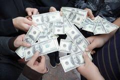 Cinco adolescentes que permanecem com divertimentos dos dólares nas mãos Fotografia de Stock Royalty Free