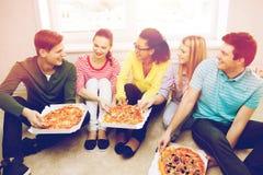Cinco adolescentes sonrientes que comen la pizza en casa Imagen de archivo libre de regalías