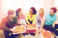 Cinco adolescentes sonrientes que comen la pizza en casa Fotos de archivo libres de regalías