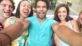 Cinco adultos jovenes que ríen mientras que toma un selfie del grupo almacen de metraje de vídeo