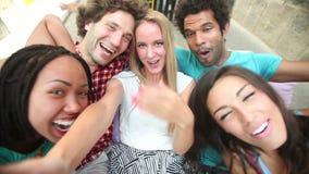 Cinco adultos jovenes que ríen mientras que toma un selfie del grupo almacen de video