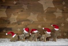 Cinco alces hechos a mano de madera con los sombreros blancos rojos de santa en un backgrou Fotos de archivo libres de regalías