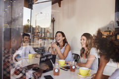 Cinco amigos adultos jovenes en un café, a través vista ventana Imágenes de archivo libres de regalías