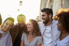 Cinco amigos adultos jovenes felices que abrazan en la calle Fotografía de archivo libre de regalías