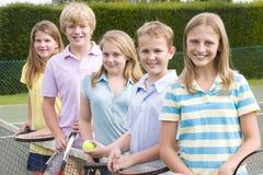 Cinco amigos jovenes en campo de tenis Foto de archivo libre de regalías