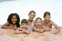 Cinco amigos jovenes en la sonrisa de la piscina fotografía de archivo