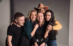 Cinco amigos jovenes frescos que se unen, abrazando, riendo y sonriendo El estudio tirado en la pared gris Foto de archivo libre de regalías