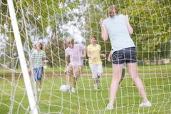 Cinco amigos jovenes que juegan a fútbol Foto de archivo