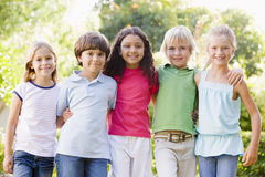 Cinco amigos jovenes que se colocan al aire libre sonrientes Imagen de archivo