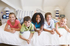 Cinco amigos novos que encontram-se para baixo ao lado de se Fotografia de Stock Royalty Free