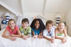 Cinco amigos novos que encontram-se para baixo ao lado de se Foto de Stock Royalty Free
