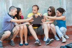 Cinco amigos que lutam sobre um portátil Fotos de Stock Royalty Free