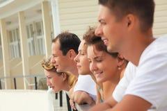Cinco amigos sonrientes en balcón Imagen de archivo libre de regalías