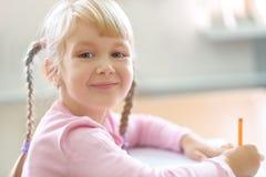 Cinco anos bonitos da menina loura idosa que senta-se na sala de aula Fotos de Stock