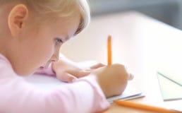 Cinco anos bonitos da menina loura idosa que senta-se na sala de aula Imagens de Stock Royalty Free