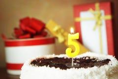 Cinco anos de aniversário Bolo com vela e os presentes ardentes Fotografia de Stock