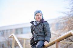 Cinco anos de menino idoso no tampão que sorri no cenário do outono imagens de stock royalty free