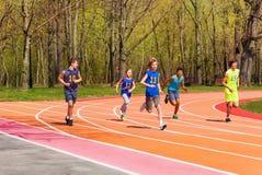 Cinco atletas adolescentes de funcionamiento en el estadio Fotografía de archivo