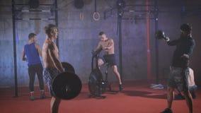 Cinco atletas fortes que fazem o treinamento do crossfit do grupo no gym vídeos de arquivo