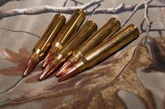 Cinco balas del rifle con un fondo del camo Foto de archivo