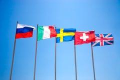 Cinco bandeiras nacionais no céu azul fotografia de stock