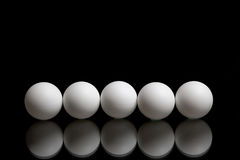 Cinco bolas para el ping-pong en fila en un fondo oscuro imágenes de archivo libres de regalías