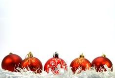 Cinco bolas rojas de la Navidad, una guirnalda blanca Imagenes de archivo