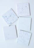 Cinco brancos de pedra diferentes das amostras principalmente baseados com mármore gostam de grões e de veias Foto de Stock Royalty Free