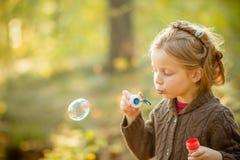 Cinco burbujas de jabón de la muchacha caucásica del niño de los años que soplan al aire libre en la puesta del sol - niñez despr fotos de archivo