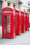 Cinco cabinas de teléfonos rojas de Londres todas en fila Fotografía de archivo libre de regalías