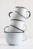 Cinco canecas esmaltadas branco Fotografia de Stock Royalty Free